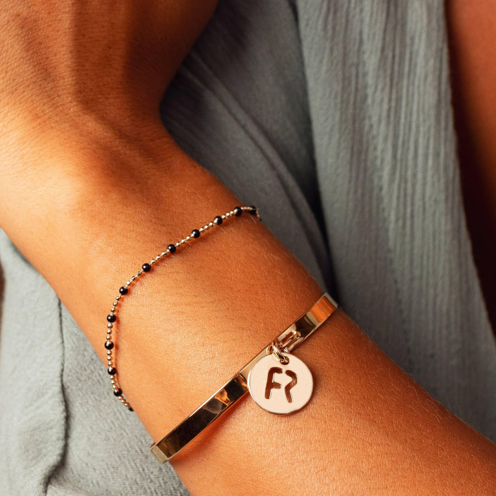 Lock bangle with perforated initial on medal