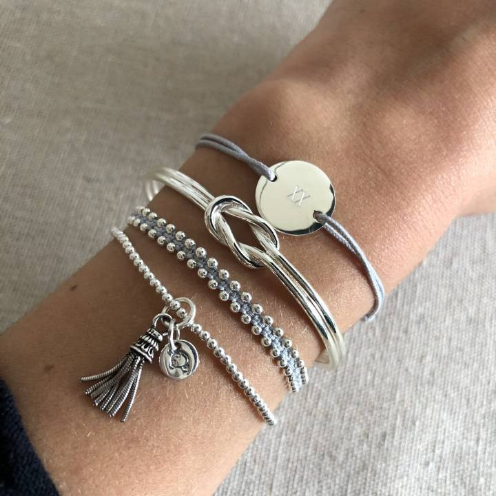 Tie bracelet with a ring